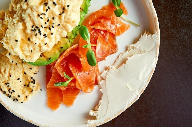 Perfektes frühstück - rührei mit lachs, avocado und frischkäse in einem weißen teller. selektiver fokus