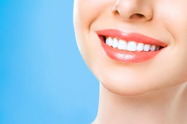 Perfektes gesundes zahnlächeln einer jungen frau. zahnaufhellung. zahnklinik patient. bild symbolisiert mundpflege zahnmedizin, stomatologie.