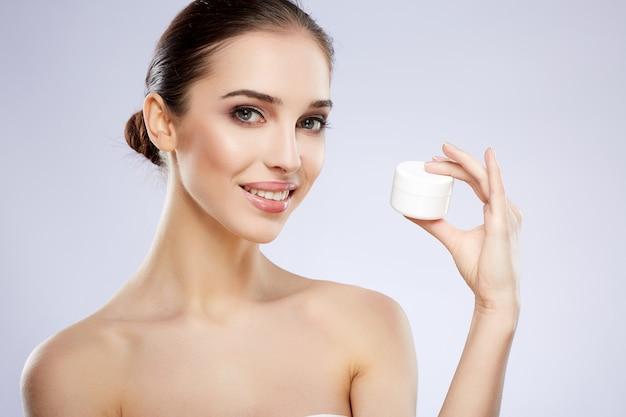 Perfektes mädchen mit nacktem make-up, das am grauen studiohintergrund, schönheitsfoto-konzept, perfekte haut, haltendes produkt, blick auf kamera und lächeln aufwirft.
