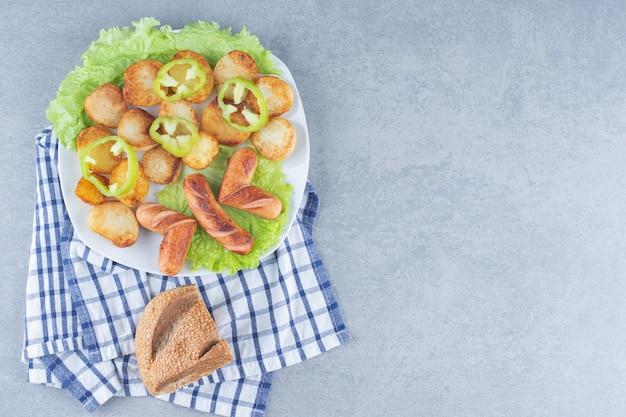 Perfektes mittagessen. wurst und kartoffel auf weißer pfanne mit brot.