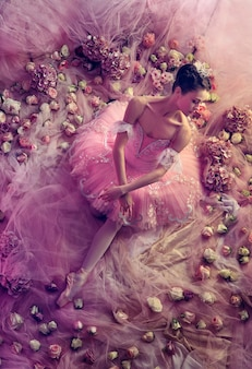 Perfektes pink. draufsicht der schönen jungen frau im rosa ballett-tutu, umgeben von blumen. frühlingsstimmung und zärtlichkeit im korallenlicht. konzept des frühlings, der blüte und des erwachens der natur.