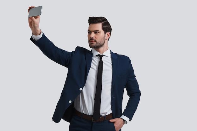 Perfektes selfie. gut aussehender junger mann in vollem anzug, der selfie mit smartphone spricht, während er vor grauem hintergrund steht