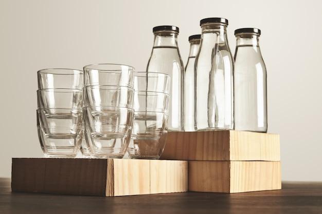 Perfektes set aus reinem, sauberem, gesundem wasser in transparenten glasflaschen und tassen auf holz