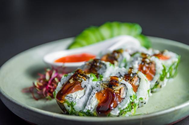 Perfektes sushi, traditionelle japanische küche. köstliches uramaki mit süß-saurer sauce auf dem verzierten teller, schwarzer hintergrund.