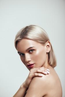 Perfektes vertikales foto einer sexy jungen frau mit blonden haaren und perfekter glänzender haut