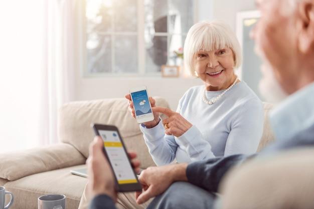 Perfektes wetter. angenehme ältere frau, die das wetter mit ihrem ehemann bespricht und ihm die mobile app mit einer vorhersage zeigt