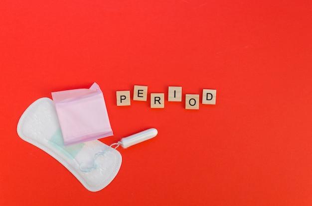 Periodenwort mit scrabblebuchstaben und auflagen und tampon