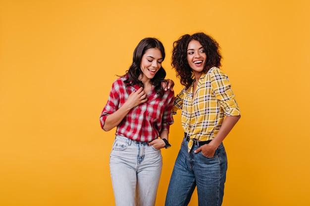 Perky girls in stylischen straßenkostümen haben spaß. brünette mit strahlendem lächeln posiert.
