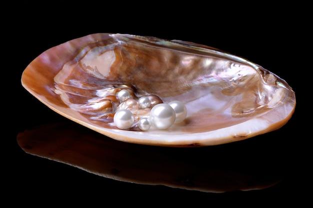 Perlen in einer schale auf einer schwarzen oberfläche