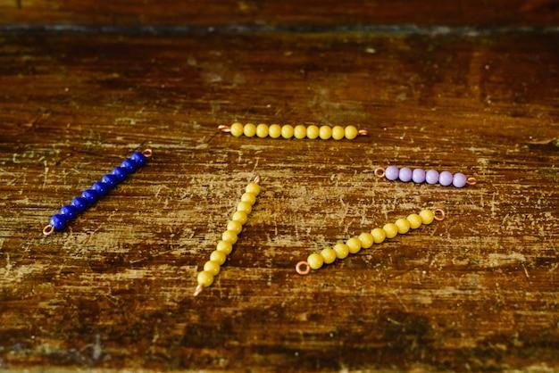 Perlen lernen, in einem montessori-klassenzimmer auf altem holz zu zählen.