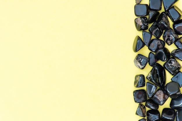Perlen, schwarze perlen auf einer draufsicht des gelben weißen hintergrundes