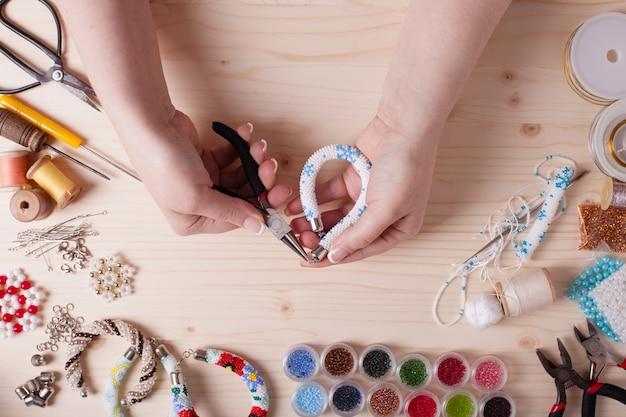 Perlen und werkzeuge zum herstellen von schmuck. vorbereitung für handarbeit. ansicht von oben