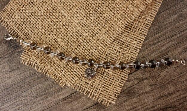 Perlenbesetztes armband auf draufsicht des hölzernen hintergrundes
