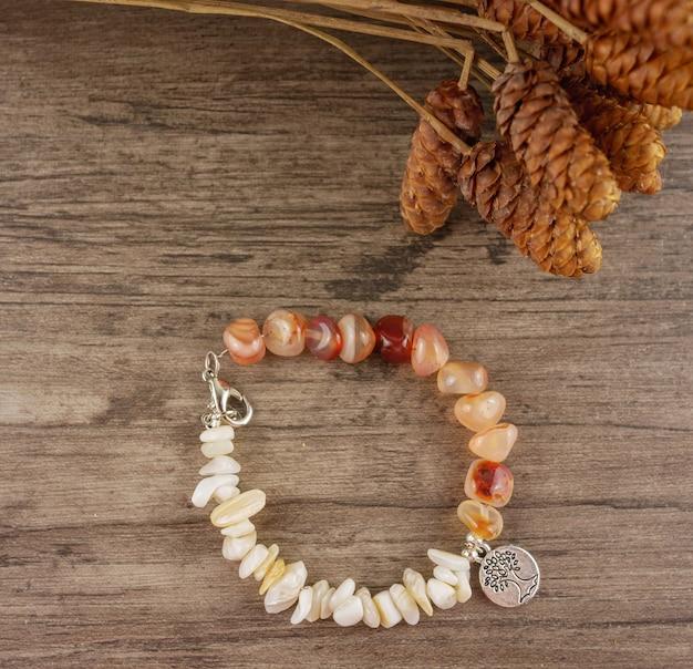 Perlenbesetztes armband auf hölzerner hintergrundebenenlage, draufsicht