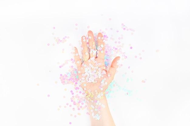 Perlenpastellkonfetti funkelt mit der frauenhand