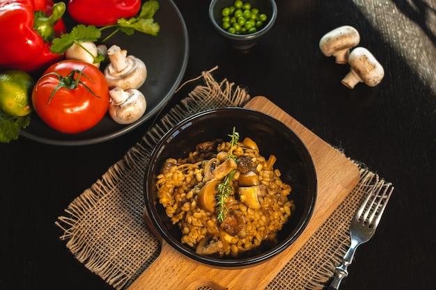 Perlgerste risotto oder orzotto mit pilzen in dunkler schüssel auf hölzernem hintergrund. selektiver fokus.
