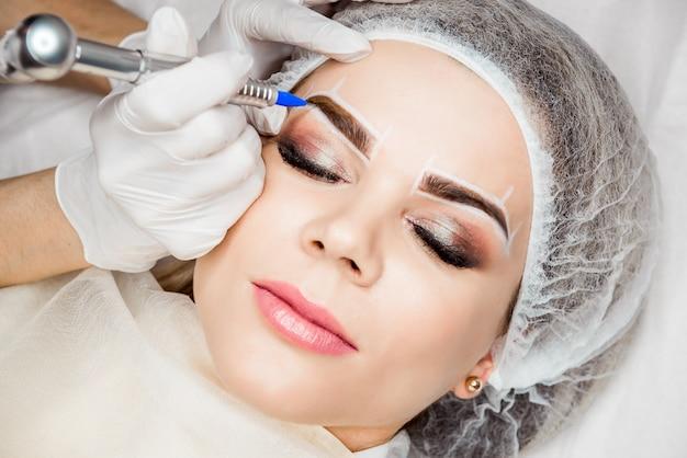 Permanent makeup für augenbrauen. nahaufnahme der schönen frau mit starken brauen im schönheits-salon. kosmetiker, der die augenbraue tätowiert für weibliches gesicht tut. beauty-prozedur.