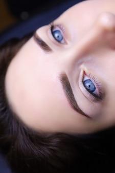 Permanente augenbrauen-make-up-nahaufnahme. modellmädchen mit blauen augen