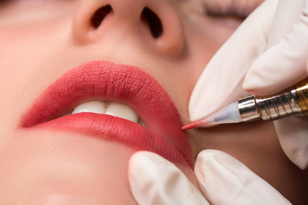 Permanente make-up-prozedur, anwendung auf junges mädchen. lippen make-up im tattoo-salon. nahaufnahme schießen.