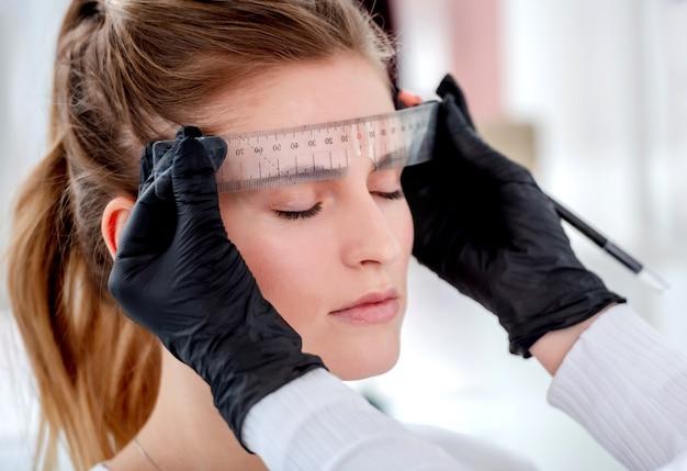 Permanenter make-up-meister misst die stirn des modells, um eine neue augenbrauenform zu zeichnen
