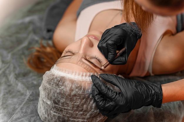 Permanentes brauenmake-up im schönheitssalon, nahaufnahme. professionelle kosmetikerin markiert die länge der augenbrauen mit einem bleistift und einem speziellen lineal zum messen der augenbrauen. kosmetologische behandlung.