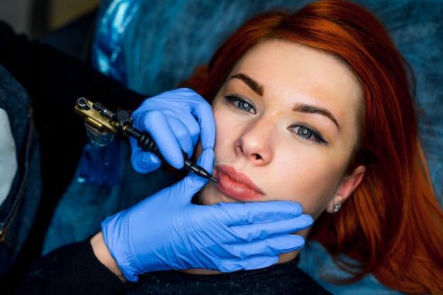 Permanentes make-up für rosa lippen für schöne frau in schönheitssalonkosmetikerin beim tätowieren auf den lippen.