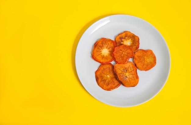 Persimmon-chips liegen auf einem porzellanteller