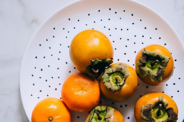 Persimone und mandarine in einer weißen platte