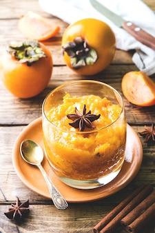 Persimonefrucht smoothie mit zimt- und anissternen, holztisch