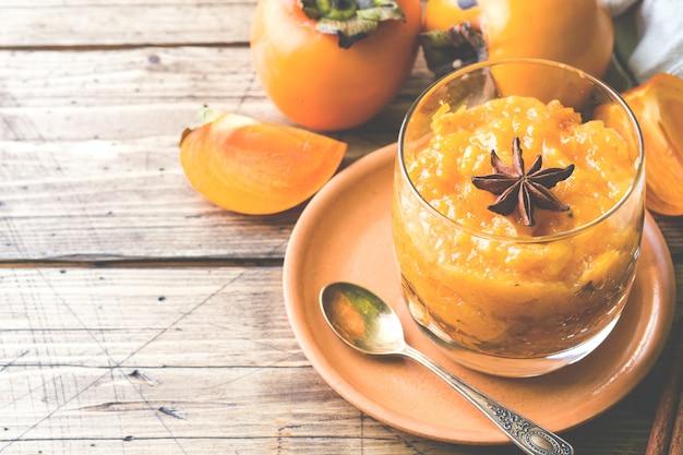 Persimonefrucht smoothie mit zimt- und anissternen, holztischkopienraum