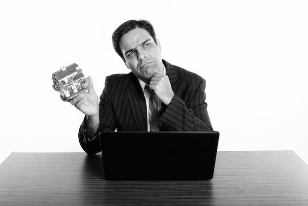 Persischer geschäftsmann, der hausfigur denkt und hält, während mit laptop auf holztisch sitzt