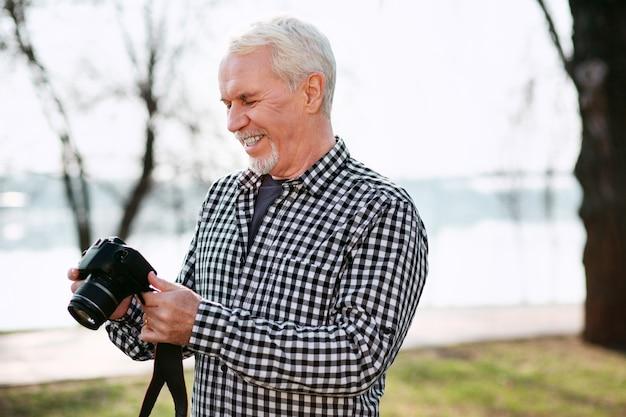 Persönliche fotos. fröhlicher älterer mann, der hinunter schaut und kamera benutzt