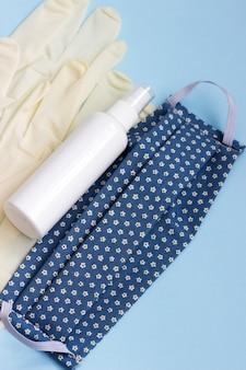 Persönliche schutzausrüstung maske, handschuhe und desinfektionsmittel auf einem blauen hintergrund.