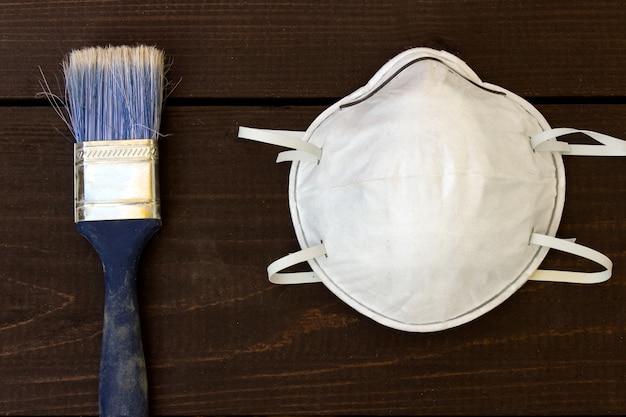 Persönliche schutzmaske und blaue bürste. arbeitssicherheit.