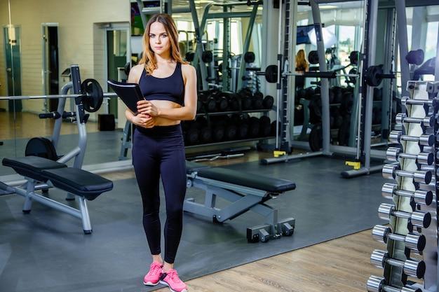 Persönliche trainerfrau, die klemmbrett mit trainingsplan in der turnhalle hält.