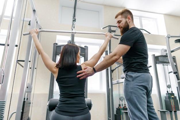 Persönlicher fitnesstrainer, der klientenfrau trainiert und hilft