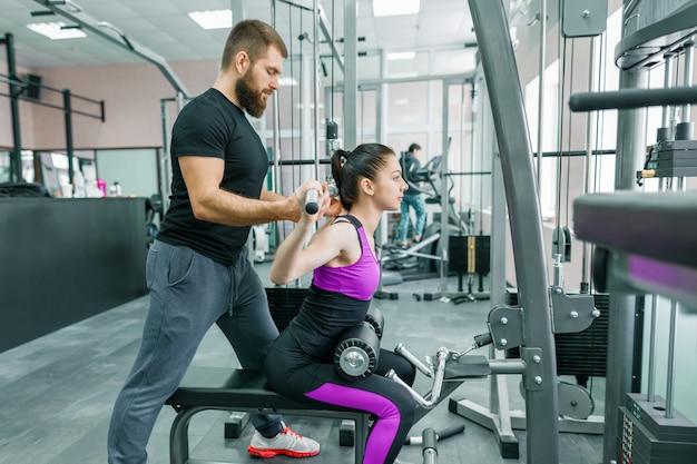 Persönlicher fitnesstrainer, der kundenfrau trainiert und hilft