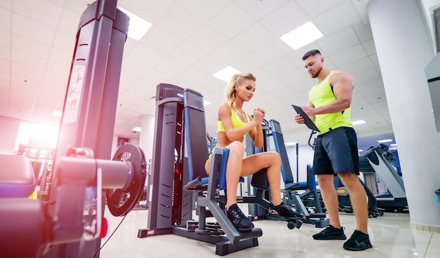 Persönlicher hübscher fitnesstrainer und schöne blonde klientin im fitnessstudio, die trainingsplan oder -programm machen.