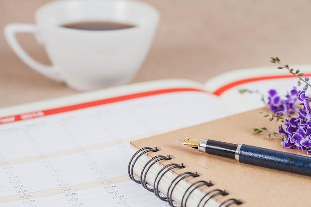 Persönlicher organisator oder planer mit füllfederhalter und heißer kaffee auf hölzerner tabelle.
