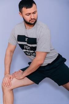Persönlicher trainer, der auf grauem hintergrund mit copyspace steht. muskulöses sportliches mann-eignungsmodell, das aufwirft.