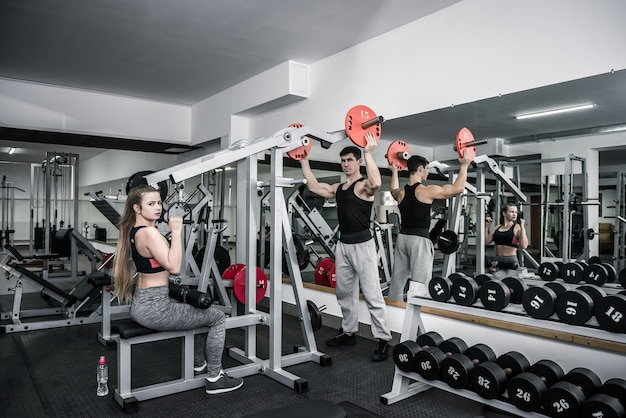 Persönlicher trainer, der der jungen frau im fitnessstudio hilft