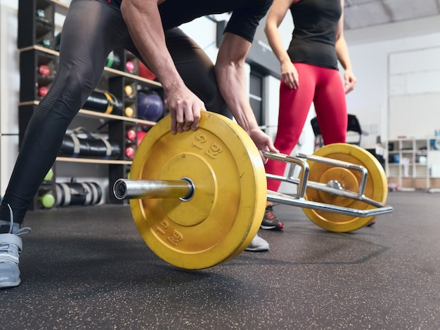 Persönlicher trainer, der eine 15 kg schwere scheibe auf die hantelstange legt, während das mädchen, das er trainiert, im hintergrund wartet.