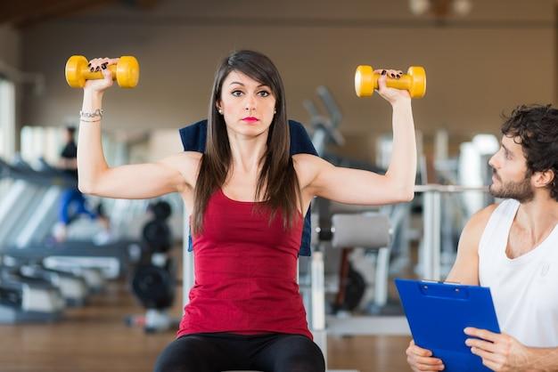 Persönlicher trainer, der eine trainingsfrau in der turnhalle betrachtet