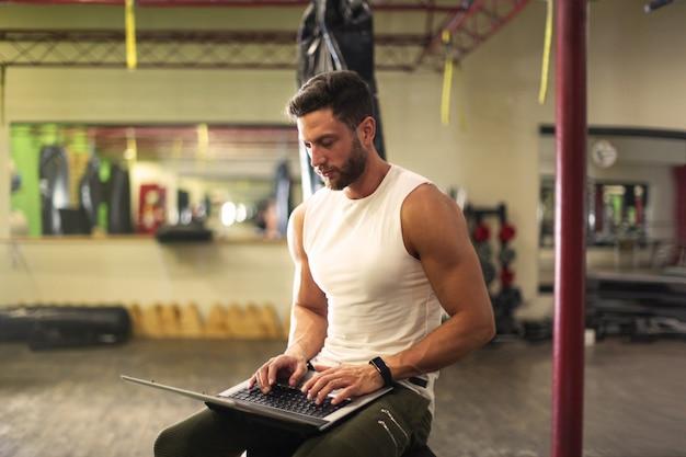 Persönlicher trainer, der einen laptop in der turnhalle verwendet