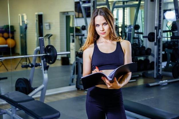Persönlicher trainer der jungen frau schreibt den trainingsplan in ein notizbuch
