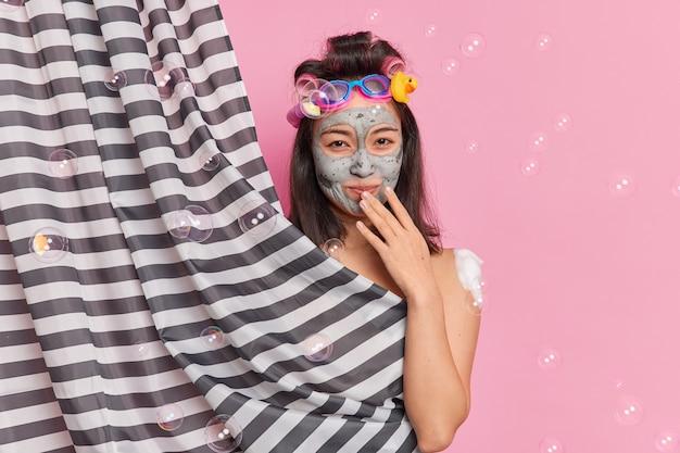 Persönliches hygiene- und pflegekonzept. zufriedene brünette frau reinigt körper nimmt regelmäßig dusche macht frisur schönheitsbehandlungen verbirgt sich hinter vorhang umgeben von fliegenden seifenblasen