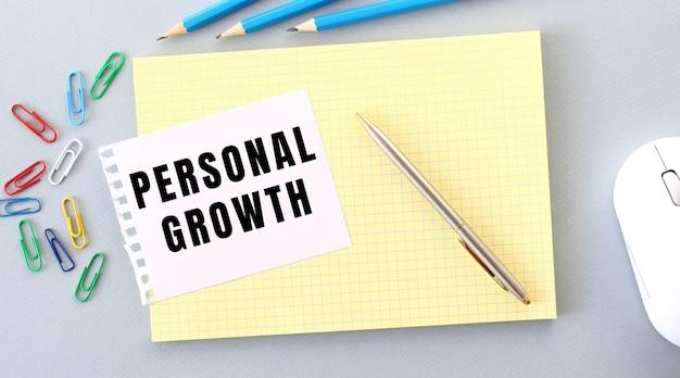 Persönliches wachstum wird auf ein stück papier geschrieben, das neben büromaterial auf einem notizbuch liegt.