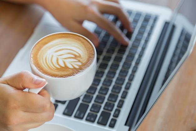 Person arbeitet an einem laptop mit einer tasse kaffee neben