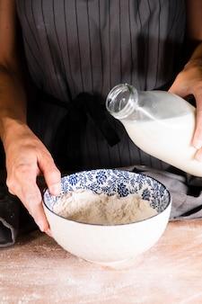 Person bereit, milch in schüssel zu gießen