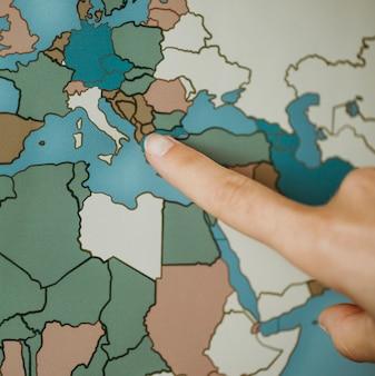 Person, die auf der karte auf europa zeigt